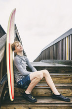 Young Teen Surfer Sitting On Boardwalk With His Surfboard