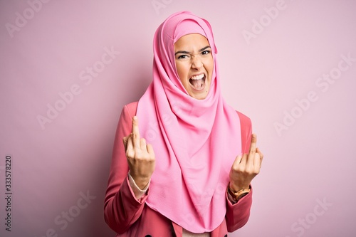 Photo Young beautiful girl wearing muslim hijab standing over isolated pink background Showing middle finger doing fuck you bad expression, provocation and rude attitude