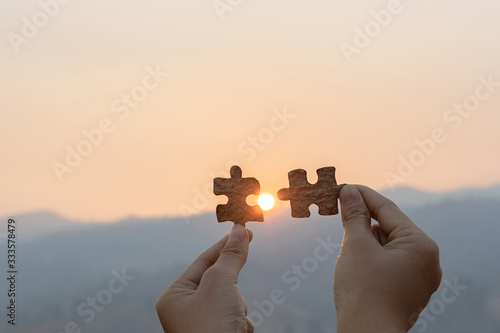 Fototapeta Closeup hand connecting jigsaw puzzle with sunset and mountains background, Business solutions, success and strategy concept obraz
