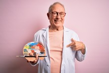 Senior Grey Haired Artist Man Painting Using Painter Palette Over Pink Background With Surprise Face Pointing Finger To Himself