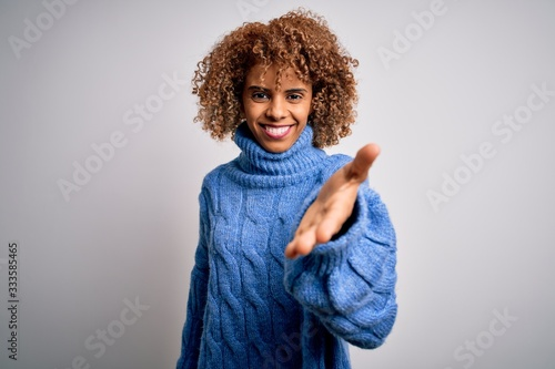 Young beautiful african american woman wearing turtleneck sweater over white background smiling cheerful offering palm hand giving assistance and acceptance Wallpaper Mural