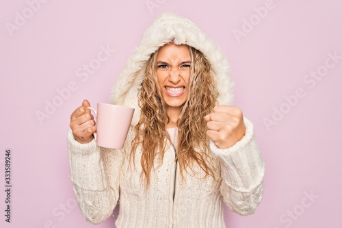 Photographie Young beautiful blonde woman wearing casual sweater with hood drinking cup of co
