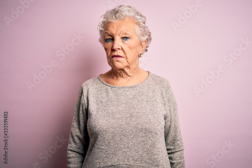Obraz Senior beautiful woman wearing casual t-shirt standing over isolated pink background looking sleepy and tired, exhausted for fatigue and hangover, lazy eyes in the morning. - fototapety do salonu