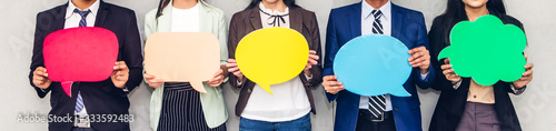 Obraz Group of business people holding a empty copyspace speech bubble icon while standing against grey background - fototapety do salonu
