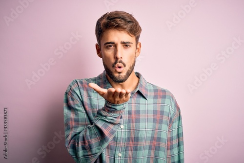 Papel de parede Young handsome man with beard wearing casual shirt standing over pink background looking at the camera blowing a kiss with hand on air being lovely and sexy