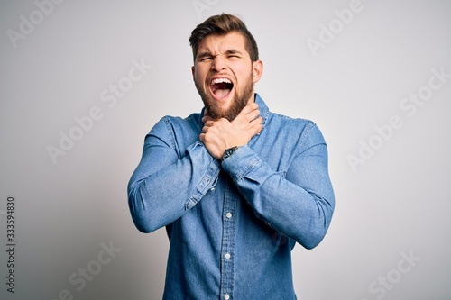 Young handsome blond man with beard and blue eyes wearing casual denim shirt shouting suffocate because painful strangle Wallpaper Mural