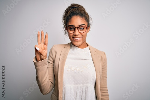 Valokuvatapetti Beautiful african american businesswoman wearing jacket and glasses over white background showing and pointing up with fingers number three while smiling confident and happy