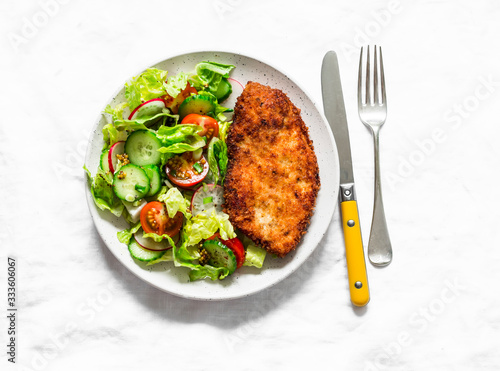 Fotografia Chicken milanese and fresh romaine salad, cherry tomatoes, radishes, cucumbers s