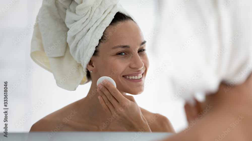 Fototapeta Pretty 30s woman reflected in mirror hold cotton pad cleanses skin, removes impurities. After shower female refreshes skin preparing it for make-up application enjoy self-care grooming process concept