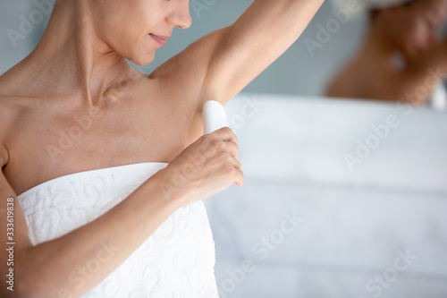 Happy 30s beautiful woman applies antiperspirant stick after shower in morning close up image Wallpaper Mural
