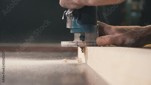 Fototapeta Carpenter chamfers edge from wooden board