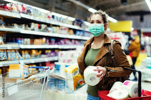 Fotografie, Tablou Woman with face mask making stock of toilet paper while buying in supermarket