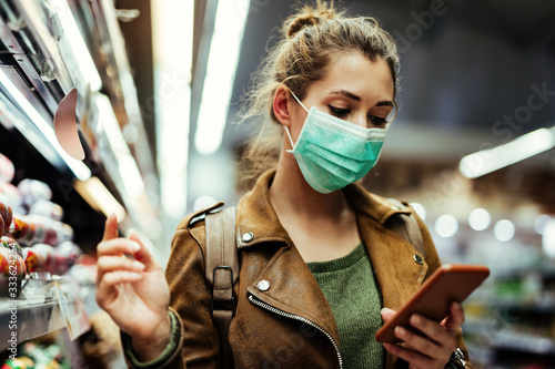 Papel de parede Woman with face mask going through check list on smart phone while buying in supermarket