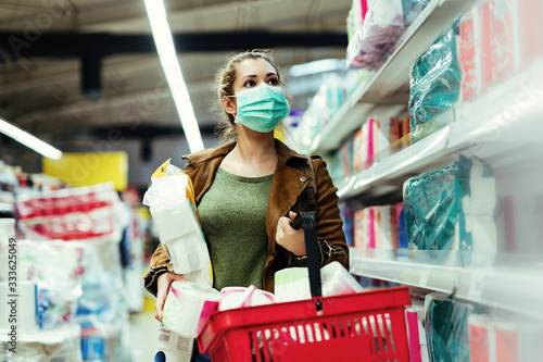 Fotografía Woman with protective face mask buying toilet paper in the store during virus epidemic