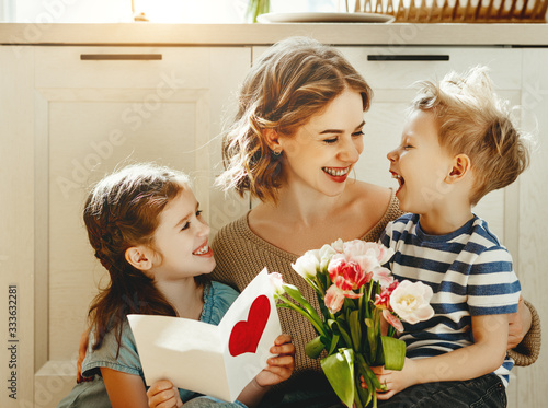 Cheerful little girl with card and youngest brother with  bouquet of tulip flowers smiling and congratulating happy mom on mother day at home Canvas Print