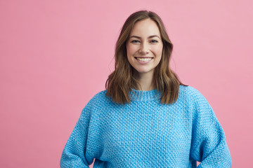 Portrait for beautiful smiling woman on a pink background, colorful portrait