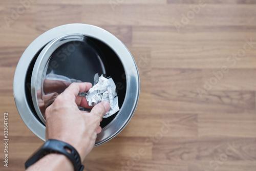 Fotografie, Obraz Hand putting crumpled bill paper in trash can