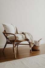 Rattan Chair And Basket, Pillows And Blanket In An Empty Room