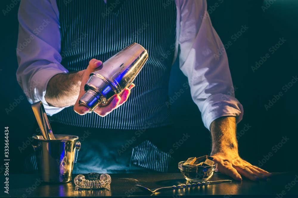 Fototapeta Bartender making cocktail, using cocktail shaker