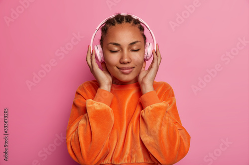 Pleased relaxed calm young woman with dark skin closes eyes, enjoys music applic Wallpaper Mural