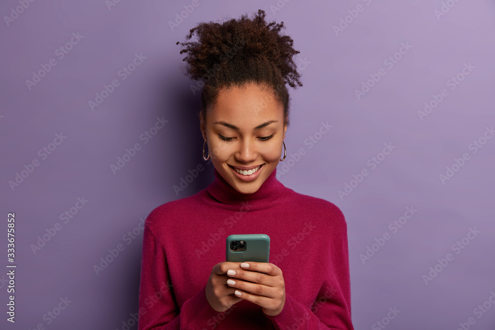 Fototapeta Happy beautiful Afro American woman uses social media messanger on modern mobile phone, chats with friends, going to have video call, dressed in casual wear, makes shopping in internet store