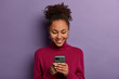 Happy beautiful Afro American woman uses social media messanger on modern mobile phone, chats with friends, going to have video call, dressed in casual wear, makes shopping in internet store