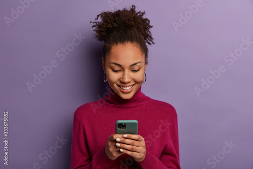 Fototapeta Happy beautiful Afro American woman uses social media messanger on modern mobile phone, chats with friends, going to have video call, dressed in casual wear, makes shopping in internet store obraz