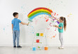Children drawing rainbow on white wall indoors