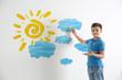 Leinwandbild Motiv Little boy drawing sun and clouds on white wall
