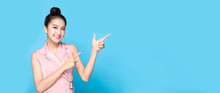 Portrait Of Asian Beautiful Young Woman Pointing Both Hands With Finger On Upper Side With Smile Face. The Pretty Girl Stand And Looking At Camera In Studio. Advertisement & Presentation Concept.