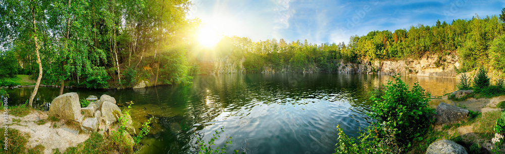 Fototapeta Panoramic landscape shot of idyllic lake surrounded by trees and cliffs, with the sun glowing on the horizon