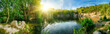 Leinwanddruck Bild - Panoramic landscape shot of idyllic lake surrounded by trees and cliffs, with the sun glowing on the horizon