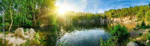 Fototapeta Panoramic landscape shot of idyllic lake surrounded by trees and cliffs, with the sun glowing on the horizon obraz
