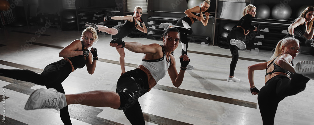 Fototapeta Women in black and white sportswear on a real group workout in the gym train to fight, kickboxing with a trainer