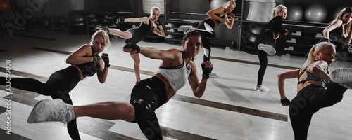 Women in black and white sportswear on a real group workout in the gym train to Fototapet