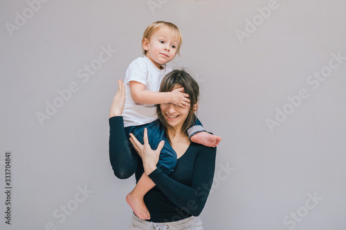 mom plays with a naughty son against a gray wall Tapéta, Fotótapéta
