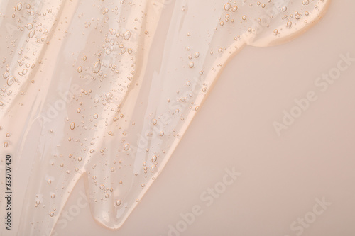 Fotografia, Obraz Pure transparent cosmetic gel on beige background, top view