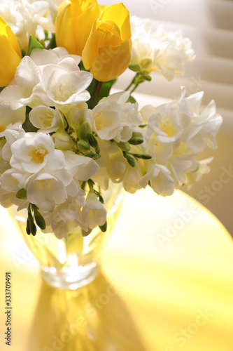 Obraz Beautiful bouquet with fresh freesia flowers in vase on table near window - fototapety do salonu