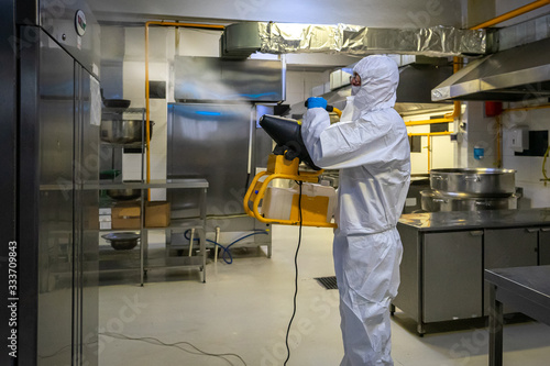 Tela man in protective equipment disinfects with a spray gun industrial surfaces due to coronavirus covid-19