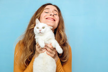 A Young Girl Is Holding A White Cat In Her Arms. Portrait Of A Curly-haired Blonde Girl On A Blue Background. The Concept Of Animal Protection. Take The Cat From The Shelter.