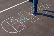 A Young Man Playing Hopscotch On Asphalt.