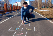 A Young Man Draws Hopscotch On Asphalt. A Man In A Medical Mask On The Street Draws Classics. The Epidemic Of Coronavirus.