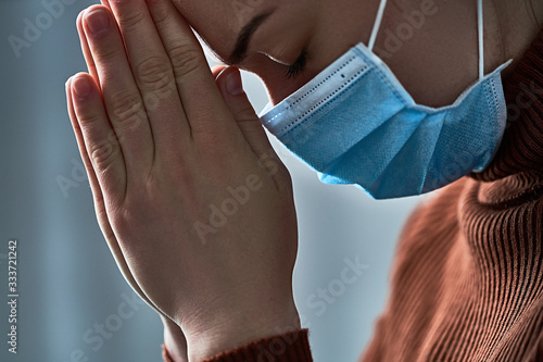 Fotografiet Woman in protective face mask with praying hands, asks god for healing and recovery during seriuos illness, coronavirus outbreak and flu covid-19 epidemic