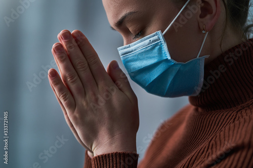 Fotografija Woman in protective mask with closed eyes and praying hands, asks god for healing and recovery during disease, coronavirus outbreak and flu covid epidemic