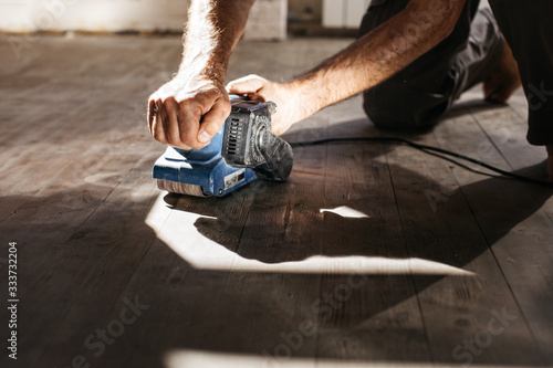 Obraz Men's hands make repairs at home. Grinding machine with a wooden floor. - fototapety do salonu