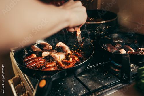 Fototapeta Frying pan overflowing with food cooking like a beast. obraz
