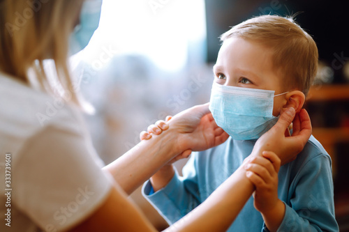 Obraz Little boy and mom in medical mask. Mother puts on her baby sterile medical mask. Child, wearing face mask, protect from infection of virus, pandemic, outbreak and epidemic of disease on quarantine. - fototapety do salonu