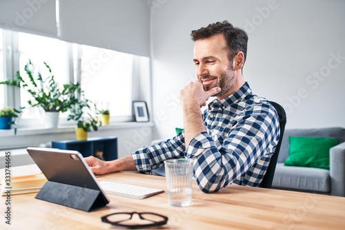 Obraz na plátně Joyful man working from home