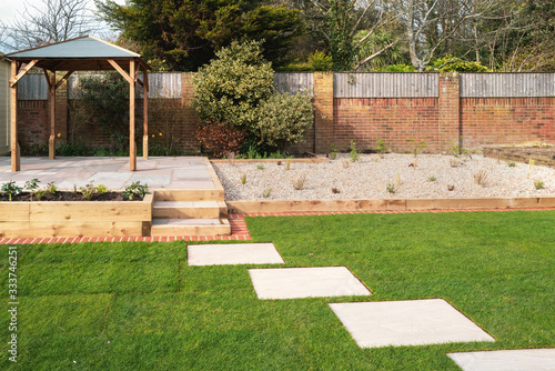 New stepping stones leading to steps and a raised patio with a wooden gazebo, next to a gravel stone planting area Wallpaper Mural