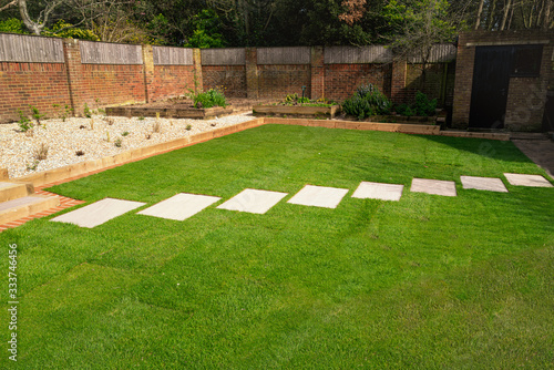 Fotomural New turf installed around a stepping stone pathway in a garden or back yard